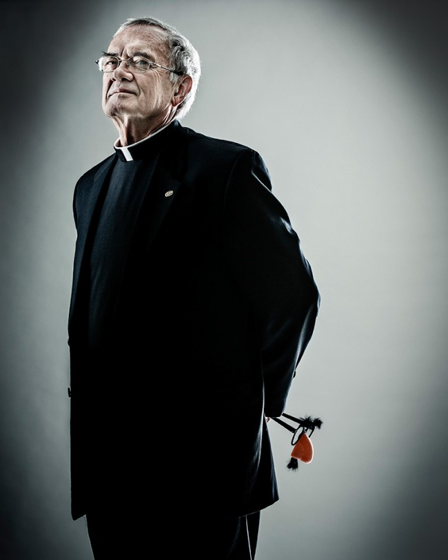"""Father John Malone, vice president for mission, poses for a portrait December 3, 2013. Malone holds a pair of """"groucho glasses,"""" representative of his sly sense of humor. Taken for St. Thomas magazine."""